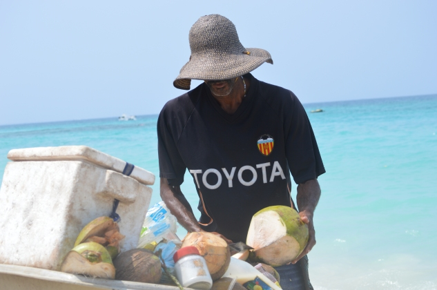 A local uses a machete to cut open a coconut on Playa Blanca.